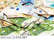 Купить «Очки на фоне денег», фото № 2016987, снято 7 февраля 2010 г. (c) Денис Миронов / Фотобанк Лори