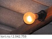 Старая электрическая лампа все еще светит уже много лет под черепичной крышей. Стоковое фото, фотограф Александр Куличенко / Фотобанк Лори