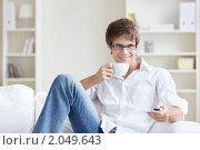 Купить «Молодой человек с пультом и чашкой кофе», фото № 2049643, снято 13 сентября 2010 г. (c) Raev Denis / Фотобанк Лори