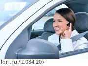 Красивая девушка водитель говорит по мобильному телефону через беспроводную гарнитуру. Стоковое фото, фотограф Сергей Петерман / Фотобанк Лори