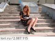 Купить «Студентка сидит возле университета и готовится к экзаменам», фото № 2087115, снято 6 августа 2009 г. (c) Олег Тыщенко / Фотобанк Лори