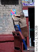 Женщина клеит плакат 1 мая (2010 год). Редакционное фото, фотограф Абушкина Мария / Фотобанк Лори