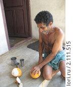Индийский рыбак режет кокос (2008 год). Редакционное фото, фотограф Зуев Алексей / Фотобанк Лори