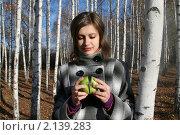 Молодая девушка в клетчатом пальто с двумя половинками зеленого яблока в руках в березовом лесу, фото № 2139283, снято 31 октября 2010 г. (c) Сергей Кузнецов / Фотобанк Лори