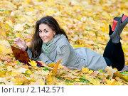 Купить «Счастливая девушка студентка лежит в осенних листьях», фото № 2142571, снято 15 октября 2010 г. (c) Дмитрий Калиновский / Фотобанк Лори