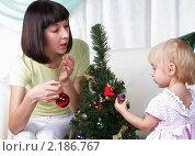 Мама и ее маленькая дочь украшают рождественскую елку. Стоковое фото, фотограф Андрей Липко / Фотобанк Лори