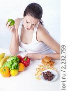 Купить «Нелегкий выбор. Девушка с овощами и сладостями», фото № 2232759, снято 1 декабря 2010 г. (c) Raev Denis / Фотобанк Лори