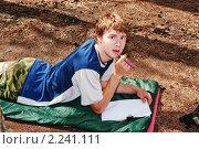 Портрет парня с ручкой и листом бумаги лежащего на спальном мешке. Стоковое фото, фотограф Вадим Кондратенков / Фотобанк Лори