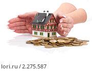 Женские руки защищают модель дома с монетами на белом фоне, в фокусе только монеты. Стоковое фото, фотограф Баевский Дмитрий / Фотобанк Лори