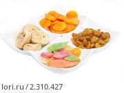 Засахаренные фрукты и еще три вида популярных сухофруктов лежат раздельно на белой тарелке на белом фоне. Стоковое фото, фотограф Андрей Алпатов / Фотобанк Лори
