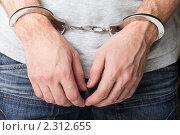Купить «Стальные наручники на руках мужчины - ограничение свободы преступников при аресте или задержании полицией», фото № 2312655, снято 5 января 2011 г. (c) Илья Андриянов / Фотобанк Лори