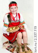 Купить «Девочка в русской народной одежде и больших лаптях сидит, держа на коленях тарелку с блинами и миску с икрой. Масленица», фото № 2337119, снято 11 февраля 2011 г. (c) RedTC / Фотобанк Лори