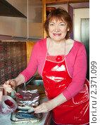 Женщина готовит скумбрию с клюквой. Стоковое фото, фотограф Яков Филимонов / Фотобанк Лори