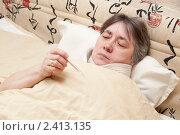 Простуженная женщина смотрит на термометр. Стоковое фото, фотограф Марина Славина / Фотобанк Лори