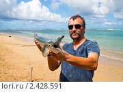 Мужчина держит в руках крупного саргана (лат. Belone belone)  с разинутой пастью. Фокус на рыбе. Стоковое фото, фотограф Ирина Кожемякина / Фотобанк Лори