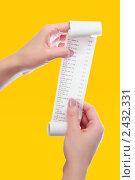 Купить «Женщина держит в руках чек в виде свитка из продуктового магазина на оранжевом фоне», фото № 2432331, снято 29 марта 2020 г. (c) AlphaBravo / Фотобанк Лори