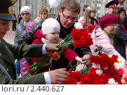 Молодой папа с дочкой возлагают цветы к Вечному огню 9 мая 2010 года в Ханты-Мансийске. Редакционное фото, фотограф Александр Овчаров / Фотобанк Лори