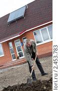 Купить «Мужчина перекапывает землю перед домом с солнечной батареей на крыше», фото № 2453783, снято 6 апреля 2011 г. (c) Виктор Филиппович Погонцев / Фотобанк Лори