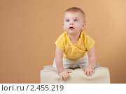 Купить «Студийный портрет девочки в жёлтой футболке на белом пуфике», фото № 2455219, снято 19 ноября 2010 г. (c) Екатерина Упит / Фотобанк Лори