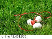 Купить «Белые яйца и ленточка с красным сердечком лежат в траве», фото № 2461935, снято 1 апреля 2010 г. (c) Иванова Марина / Фотобанк Лори
