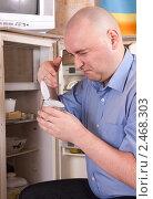Мужчина достал испорченную тушенку из открытого холодильника. Стоковое фото, фотограф Дарья Филимонова / Фотобанк Лори
