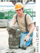 Купить «Строитель-каменщик мостит брусчаткой тротуар», фото № 2491403, снято 12 декабря 2019 г. (c) Дмитрий Калиновский / Фотобанк Лори