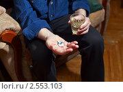 Старый мужчина держит стакан с водой и таблетки. Стоковое фото, фотограф Анна Лурье / Фотобанк Лори