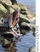 Купить «Девочка пускает в море бумажный кораблик», фото № 2571675, снято 2 июня 2011 г. (c) RedTC / Фотобанк Лори