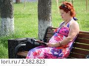 Купить «Беременная женщина читает на свежем воздухе», фото № 2582823, снято 3 июня 2011 г. (c) Оксана Лычева / Фотобанк Лори