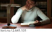 Купить «Молодой человек читает книгу за рабочим столом. Снято слайдером.», видеоролик № 2641131, снято 28 февраля 2011 г. (c) ILLYCH / Фотобанк Лори
