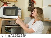 Купить «Беременная девушка готовит в микроволновой печи», фото № 2662359, снято 29 мая 2011 г. (c) Михаил Ворожцов / Фотобанк Лори