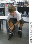 Мальчик примеряющий ролики в спортивном магазине. Стоковое фото, фотограф Ольга Шевченко / Фотобанк Лори