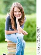 Купить «Студентка сидит на стопке учебников», фото № 2765087, снято 10 июля 2011 г. (c) Константин Ёлшин / Фотобанк Лори