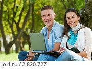 Купить «Молодая пара в парке с ноутбуком», фото № 2820727, снято 21 октября 2018 г. (c) Дмитрий Калиновский / Фотобанк Лори