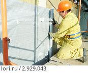 Купить «Рабочий на стройке устанавливает наружную теплоизоляцию», фото № 2929043, снято 23 мая 2019 г. (c) Дмитрий Калиновский / Фотобанк Лори