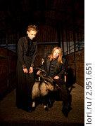 Молодая женщина и мужчина в черном готическом наряде с овцой в хлеву. Стоковое фото, фотограф Литвак Илья Леонидович / Фотобанк Лори
