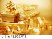 Купить «Золотистые новогодние украшения и подарок на абстрактном фоне», фото № 2953019, снято 23 сентября 2010 г. (c) Иван Михайлов / Фотобанк Лори