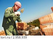 Строитель в каске кладет кладку на фоне голубого неба. Стоковое фото, фотограф Дмитрий Калиновский / Фотобанк Лори