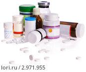 Купить «Баночки с лекарственными препаратами и рассыпанные таблетки на белом фоне», фото № 2971955, снято 13 октября 2011 г. (c) Gennadiy Poznyakov / Фотобанк Лори