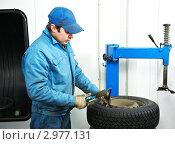 Купить «Шиномонтажник на рабочем месте. Мужчина измеряет давление в колесе автомобиля», фото № 2977131, снято 27 марта 2019 г. (c) Дмитрий Калиновский / Фотобанк Лори