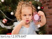 Купить «Маленькая девочка дошкольного возраста красит губы, смотрясь в детское розовое зеркало на фоне новогодней елки», фото № 2979647, снято 24 сентября 2018 г. (c) Ольга Хорькова / Фотобанк Лори