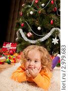 Купить «Маленькая девочка лежит на пушистом ковре у новогодней елки с подарками», фото № 2979683, снято 24 сентября 2018 г. (c) Ольга Хорькова / Фотобанк Лори