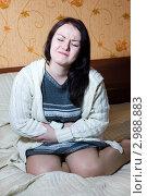 Молодая женщина скривилась от боли в животе, сидя дома на кровати. Стоковое фото, фотограф Darkbird77 / Фотобанк Лори