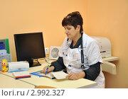 Врач-педиатр в рабочем кабинете делает запись в карточке пациента (2011 год). Редакционное фото, фотограф Анна Мартынова / Фотобанк Лори