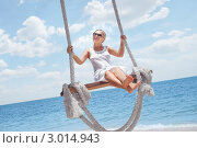 Купить «Счастливая девушка в белом платье и солнцезащитных очках на качелях над морем», фото № 3014943, снято 2 сентября 2011 г. (c) Дмитрий Эрслер / Фотобанк Лори