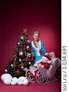 Купить «Снегурочка и ребенок в костюме Санты в санях около новогодней елки на красном фоне», фото № 3034691, снято 29 марта 2020 г. (c) Гурьянов Андрей / Фотобанк Лори