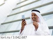 Радостный восточный бизнесмен говорит по сотовому телефону рядом с офисным зданием. Стоковое фото, фотограф Monkey Business Images / Фотобанк Лори