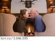 Купить «Пожилая пара целуется в креслах у камина», фото № 3046595, снято 5 октября 2007 г. (c) Monkey Business Images / Фотобанк Лори