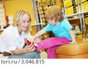 Купить «Мама примеряет маленькой дочке новые туфельки в магазине», фото № 3046815, снято 18 января 2020 г. (c) Дмитрий Калиновский / Фотобанк Лори