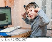 Купить «Счастливый мальчик в наушниках сидящий за компьютером», эксклюзивное фото № 3052567, снято 10 декабря 2011 г. (c) Игорь Низов / Фотобанк Лори